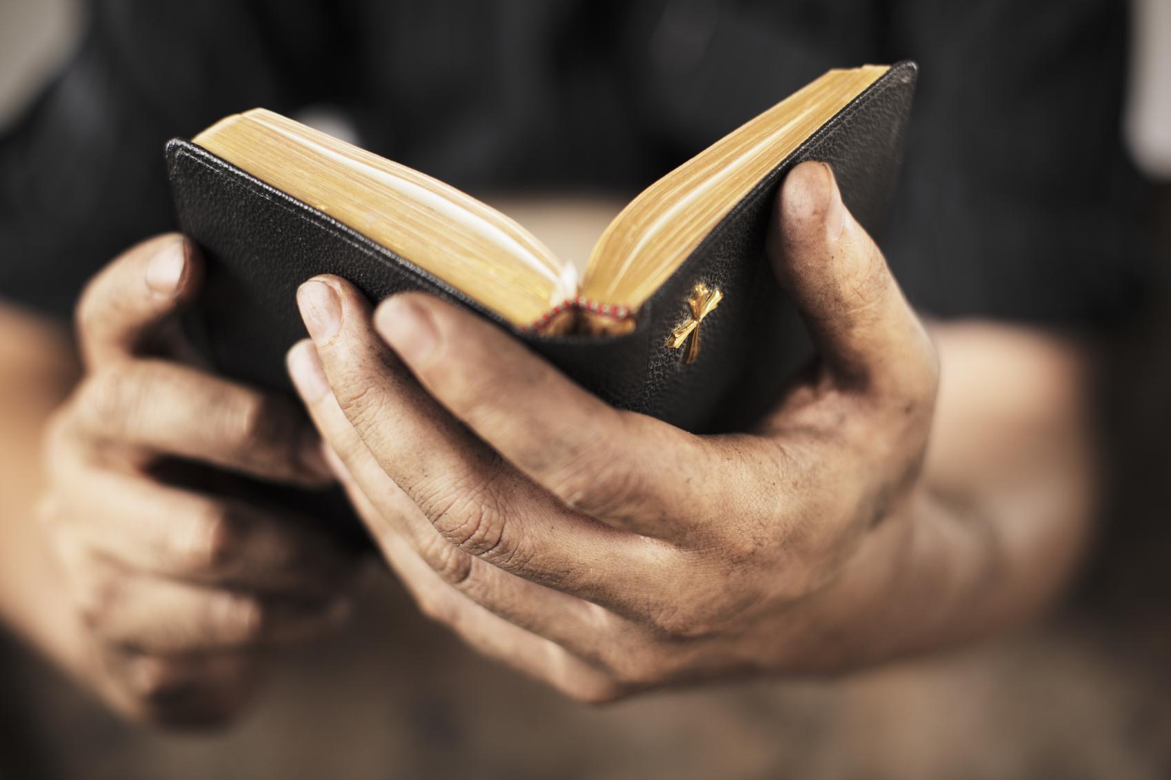 Hands holding open Bible